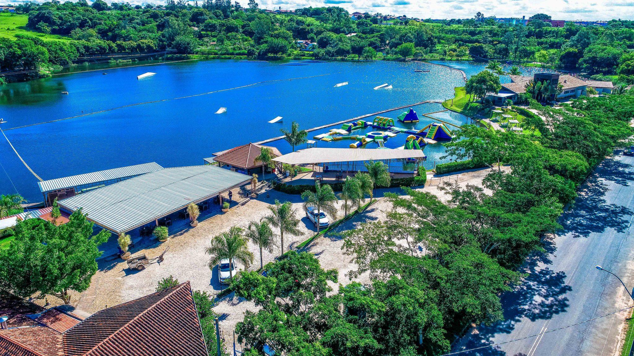 Vista aérea do lago do Naga Cable Park mostrando o quiosque, o Naga Floats e o Full Size